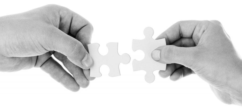 Dos manos con piezas de puzzle