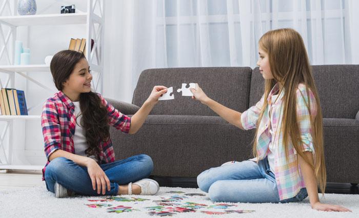 Niñas divirtiéndose jugando con un puzzle